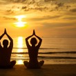 Young couple practicing yoga on the sea beach at sunset — Stock Photo #16623365