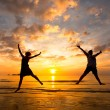 Young couple in a jump on the sea beach at sunset — Stock Photo