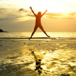 Silhouette of young girl, jumping against of sea sunset — Stock Photo