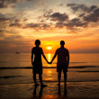 Young couple holding hands on the sea beach at sunset — Stock Photo