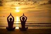 Ungt par utövar yoga på havsstranden vid solnedgången — Stockfoto