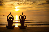 Young couple practicing yoga on the sea beach at sunset — Stok fotoğraf