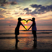Young couple holding hands heart-shaped on the sea beach at sunset — Stock Photo