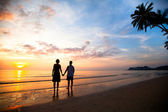 A young couple in love holding hands at sunset at the seaside — Stock Photo