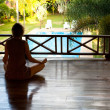 Young woman sitting in lotus position with the balcony looking at the pool in the spa resort — Foto de Stock