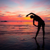 Young woman doing exercise on the beach — Стоковое фото