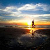 在一个美丽的黄昏期间练瑜伽在海滩上的女人的剪影. — 图库照片