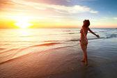 Una mujer joven se encuentra en la playa durante un hermoso atardecer — Foto de Stock