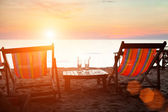 Deckchairs on the beach at sunset — Foto de Stock