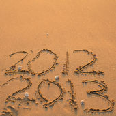 Inscription 2012 and 2013 on a beach — Stock Photo