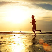 Silhouette of a young woman jogger at sunset on the seashore — Stock Photo
