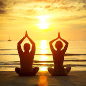 Young couple practicing yoga on the beach at sunset — Stock Photo