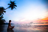 Beautiful woman doing lotus yoga pose on the beach near the ocean at sunset in Thailand — Stock Photo
