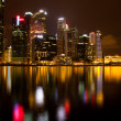 Stock Photo: City of Singapore at night, Marina Bay with water reflections.