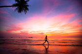 Beautiful sunset with silhouettes of girls on a beach jogger — Stock Photo