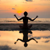 Yoga woman sitting in lotus pose on the beach during sunset, with reflection in water. — Stock Photo