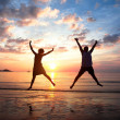Stock Photo: Concept of long-awaited vacation: Young couple in jump on sebeach at sunset.