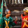 Stock Photo: an unidentified cambodians in national dress poses for tourists in angkor wat