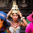 An unidentified girl in national dress poses for tourists in Angkor Wat - Stock Photo