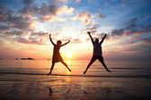 Concept of long-awaited vacation: Young couple in a jump on the sea beach at sunset. — Stok fotoğraf