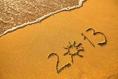 2013 written in sand on beach texture — Stock Photo