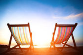 Pair of beach loungers on the deserted coast sea at sunrise, perfect vacation concept — Stock Photo