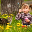 Funny lovely little girl and a cat, blowing soap bubbles — Stock Photo