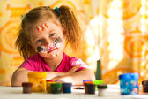 Little artist, drawing paint with paint of face. — Stock Photo