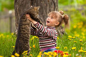 Funny lovely little girl playing with a cat — Stock Photo