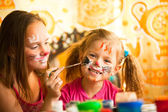 Young sisters playing with painting — Stock Photo