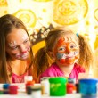 Stock Photo: Young sisters playing with painting.