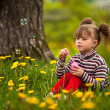 Funny lovely little five-year girl blowing soap bubbles in the park — Photo
