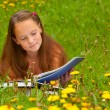 A girl 11 years old reads a book in the meadow — Stock Photo