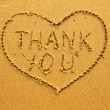 Texture of sand: the inscription inside the heart of Thank You. - Stockfoto