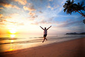 Young fun man running on sea beach at sunset — Stock Photo