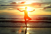 Young woman practicing yoga on the beach in the Siam Gulf during the sunset — Stock Photo