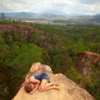 Young girl lying on top of the rock in the canyon, picture of loneliness. — Photo