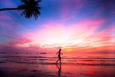 美しいサンセット ビーチ ジョガー上の女の子のシルエットを. — ストック写真