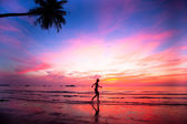 Beautiful sunset with silhouettes of girls on a beach jogger. — Stock Photo
