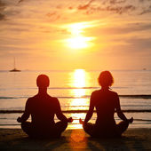 Yoga practice, young couple sitting on the beach of the sea in the lotus position at sunset — Stock Photo