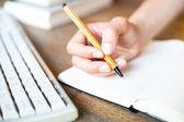 Hände schreibt einen stift in einem notizbuch (computer-tastatur, einen stapel bücher im hintergrund) — Stockfoto