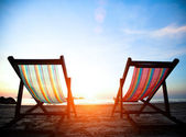 Vacation concept: Pair of beach loungers on the deserted coast sea at sunrise. — Stock Photo