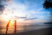 年轻夫妇心形海沙滩上在日落时手牵手. — 图库照片