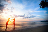 Young couple holding hands heart-shaped on the sea beach at sunset. — Foto de Stock