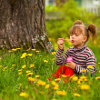 Beautiful funny lovely little five-year girl blowing soap bubbles in the park — Stock Photo