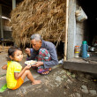 BALI - APRIL 3: Unidentified poor child eats with his father during a break working on the farm on April 3, 2012 on Bali. Daily caloric intake per capita in Indonesia is 2891 kcal per person. — ストック写真