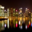 A view of Singapore business district in the night time with water reflections. — Foto de Stock