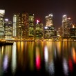 Stock Photo: A view of Singapore business district in the night time with water reflections.