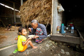 BALI - APRIL 3: Unidentified poor child eats with his father during a break working on the farm on April 3, 2012 on Bali. Daily caloric intake per capita in Indonesia is 2891 kcal per person. — Stock Photo