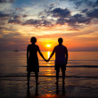 Silhouettes young couple on beach at sunset, romantic picture — Foto Stock #19635301